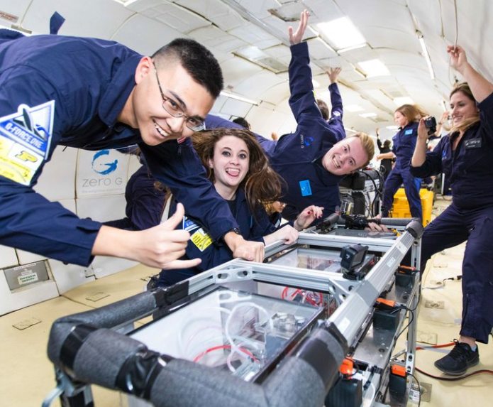 Image Description: Large group of smiling students perform a research experiment while floating inside the ZERO-G plane. Credit: ZERO-G.