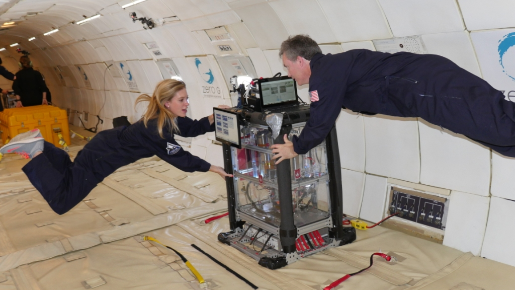 Two researchers float during a ZERO-G flight while holding on to a large rectangular experiment apparatus. This research was conducted by Carthage College. Credit: ZERO-G.